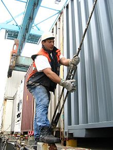 220px Dockworker lashing a container How Container Ships Crew Can Help in Preventing Injuries to Stevedores?