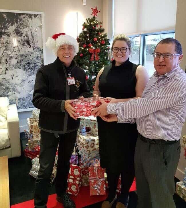 John Webb and Holly Hughes handing parcels to Paul Atkinson (in Santa hat).