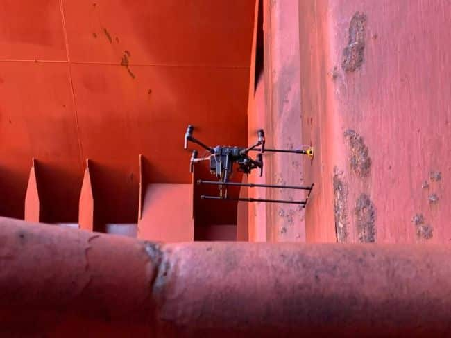Airborne drone conducting ultrasonic thickness measurements inside the hold of a bulk carrier