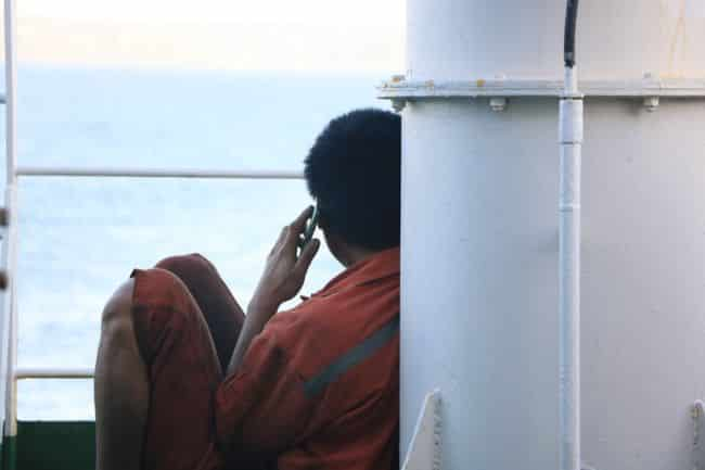 Seafarer sitting aboard, calling his family