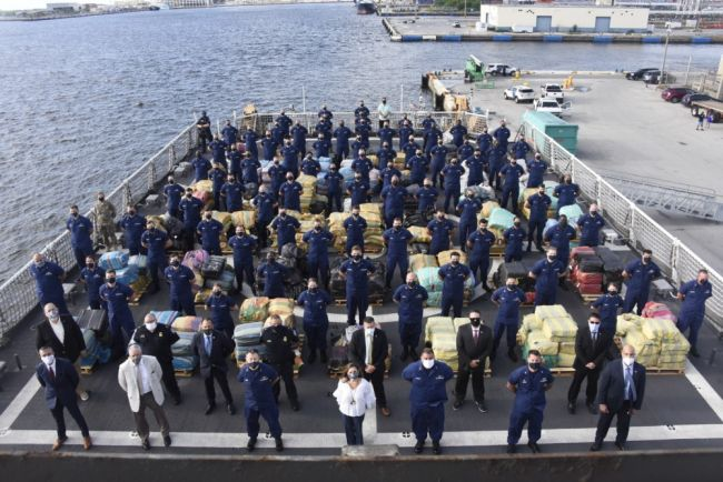 The Coast Guard Cutter Hamilton (WMSL 753) crew stands amongst approximately 11,500 pounds of cocaine and approximately 17,000 pounds of marijuana, Aug. 27