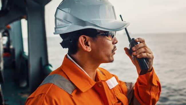 Filipino deck Officer on deck of vessel or ship , wearing PPE personal protective equipment. He speaks to VHF walkie-talkie radio in hands. Dream work at sea