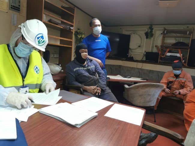 An ITF inspector checking the vessel's paperwork on board - Source ITF