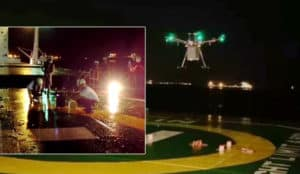 drone in picture delivering load to the vessel at anchorage at night