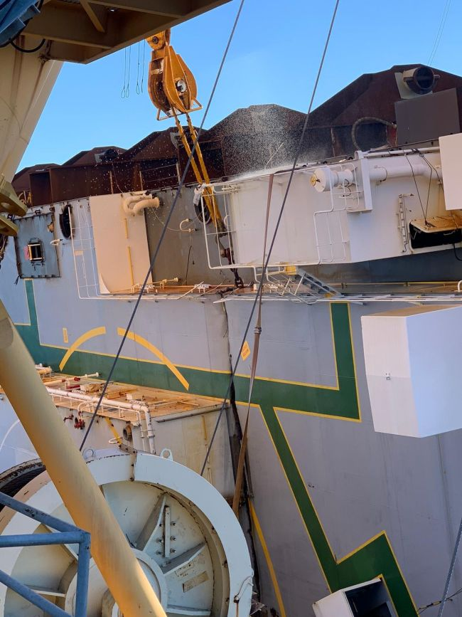 Cooled by water, the cutting chain progresses through the deck of the Golden Ray wreck