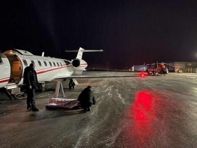 carries an injured man toward an awaiting Guardian Flight Alaska aircraft crew in Cold Bay, Alaska, Wednesday, Dec. 30, 2020.