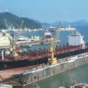 A large tanker ship is being renovated in shipyard