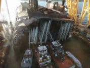 Tugs use fire monitors to control a fire inside the Golden Ray wreck