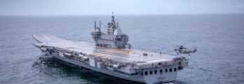 Indegenious aircraft carrier Vikrant sailing out for sea trials, with a helicopter hovering above it