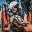 A Rescuer with a baby in her hands onboard